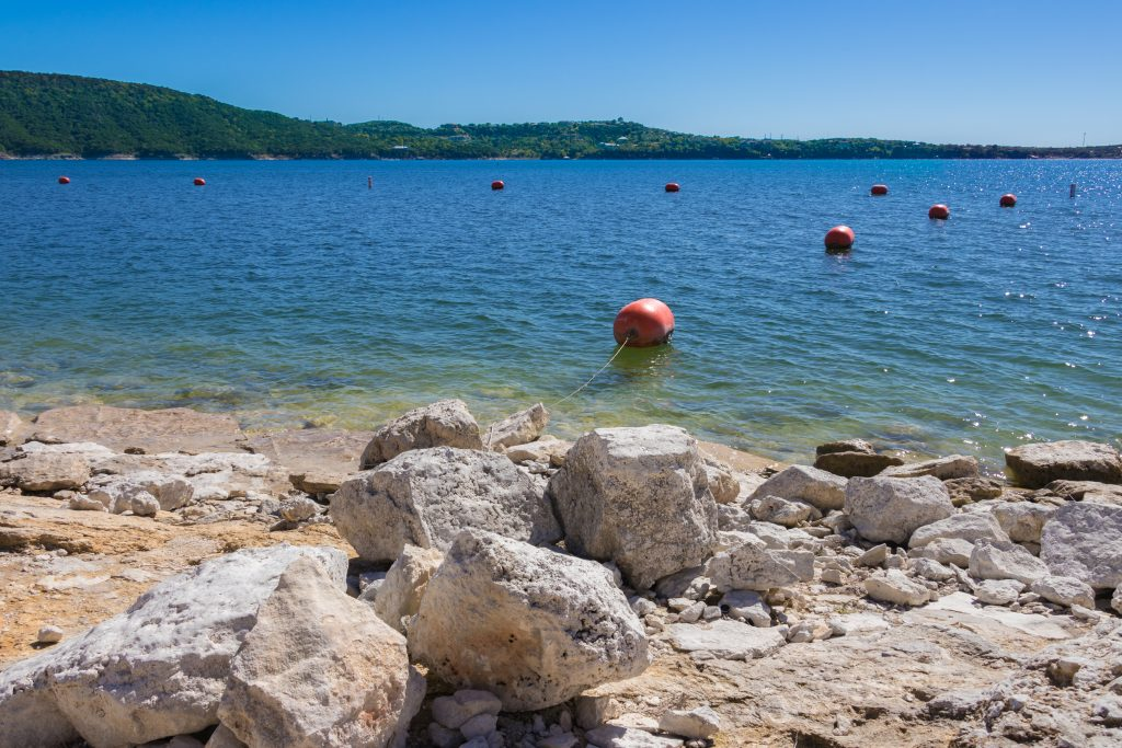 rocky beach on lake travis with swimming bouys on the water, best austin beaches guide