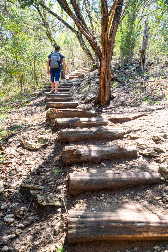 jeremy storm climbing a long staircase of wooden steps when hiking river place nature trail austin
