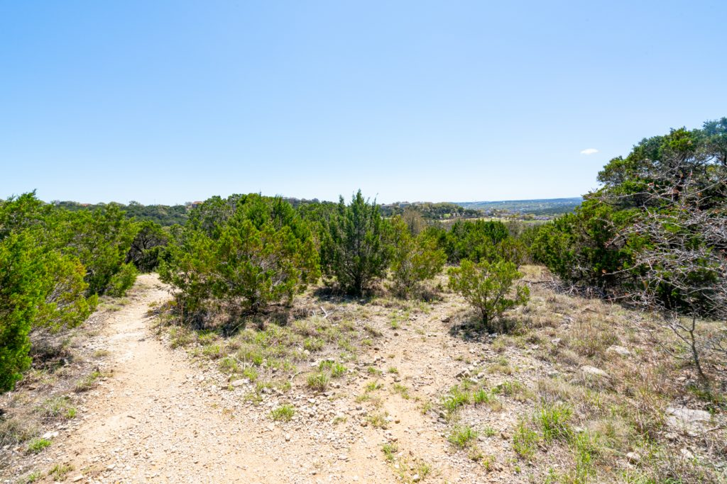 sunny upper portion of trail with texas hill country in background
