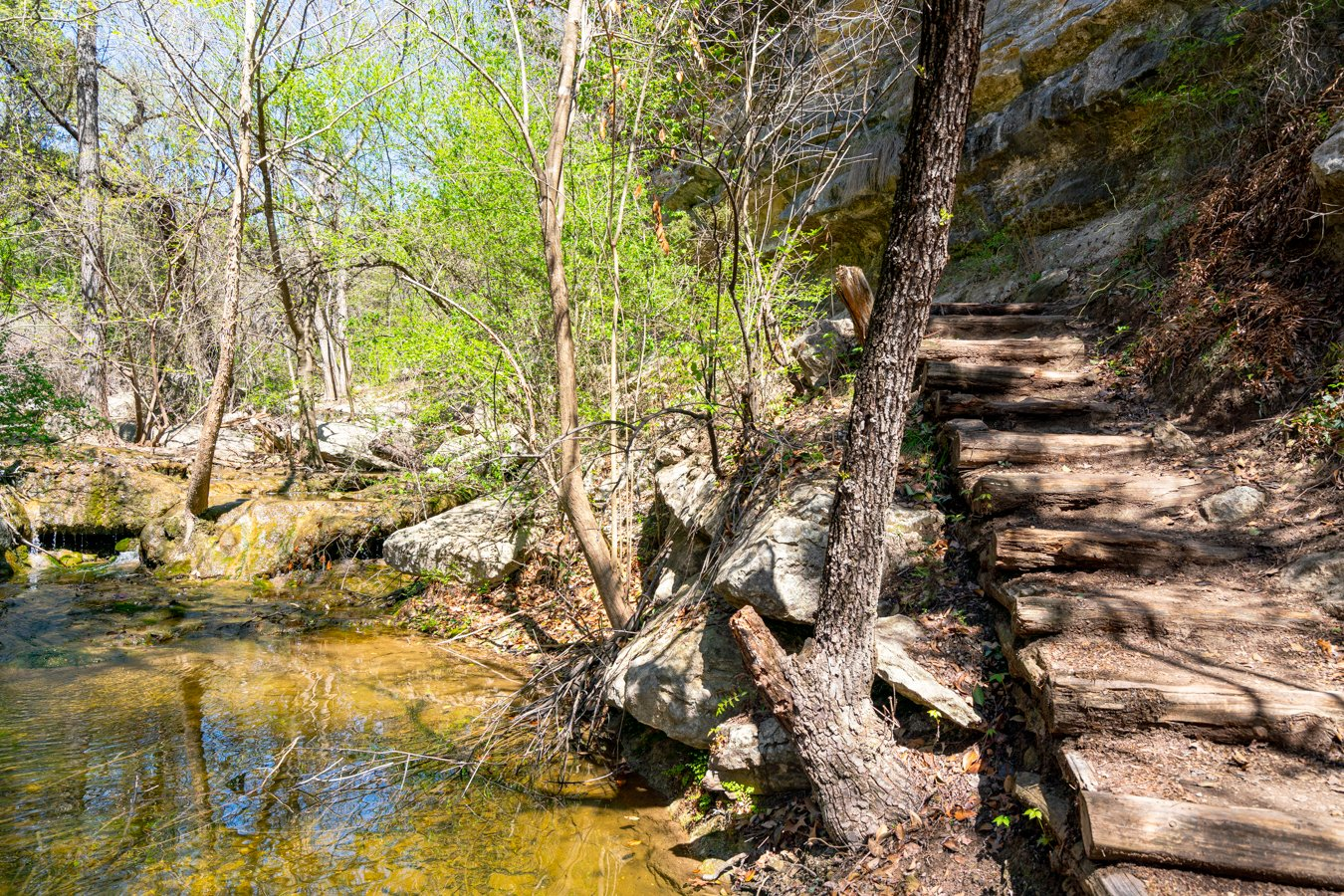 hiking steps of river place nature trail austin with small waterfall to the left