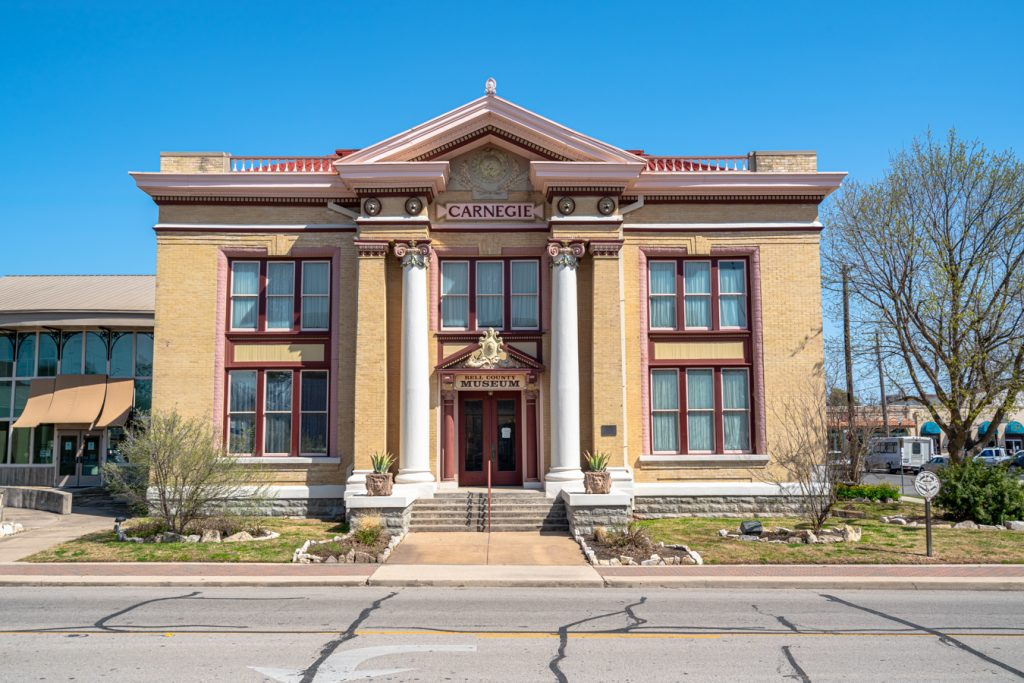 front facade of the carnegie library that holds the bell county museum, with 2 white columns flanking the door