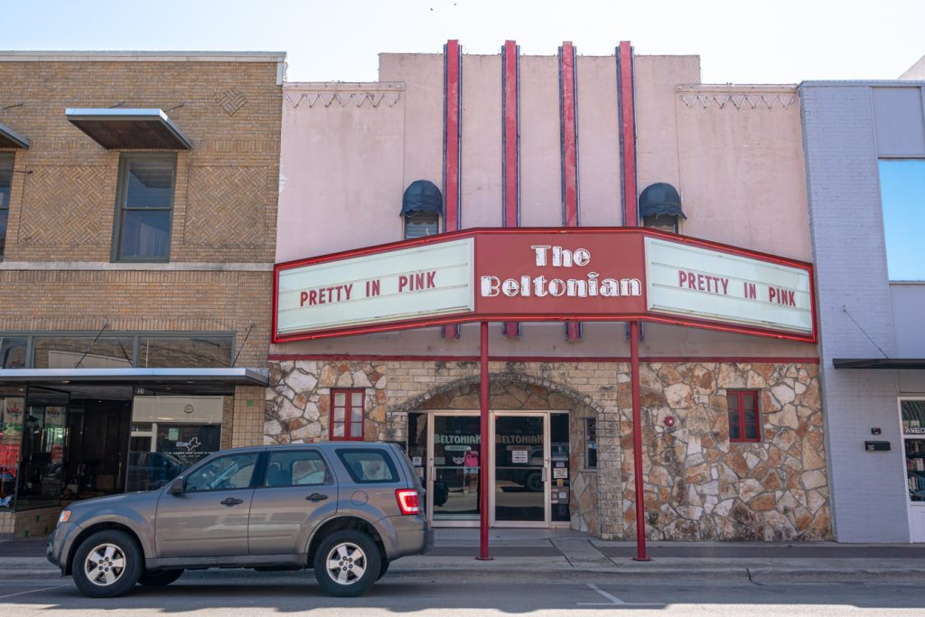 front facade of the pink belatonian theatre in belton texas, with a simple red and white marquee