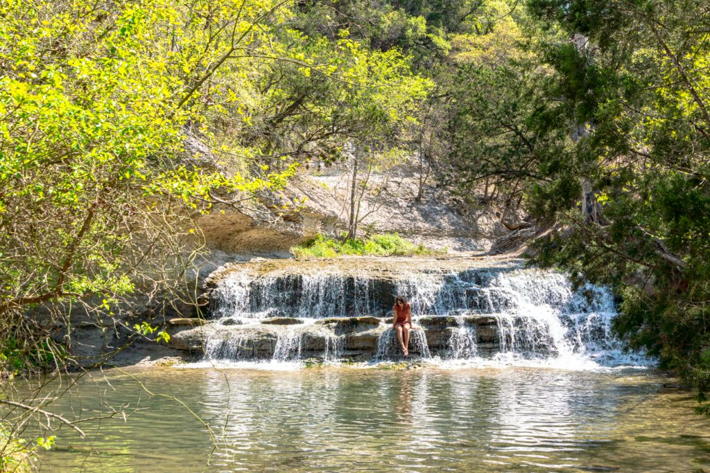 young woman sitting in the center of the falls at chalk ridge falls park belton texas