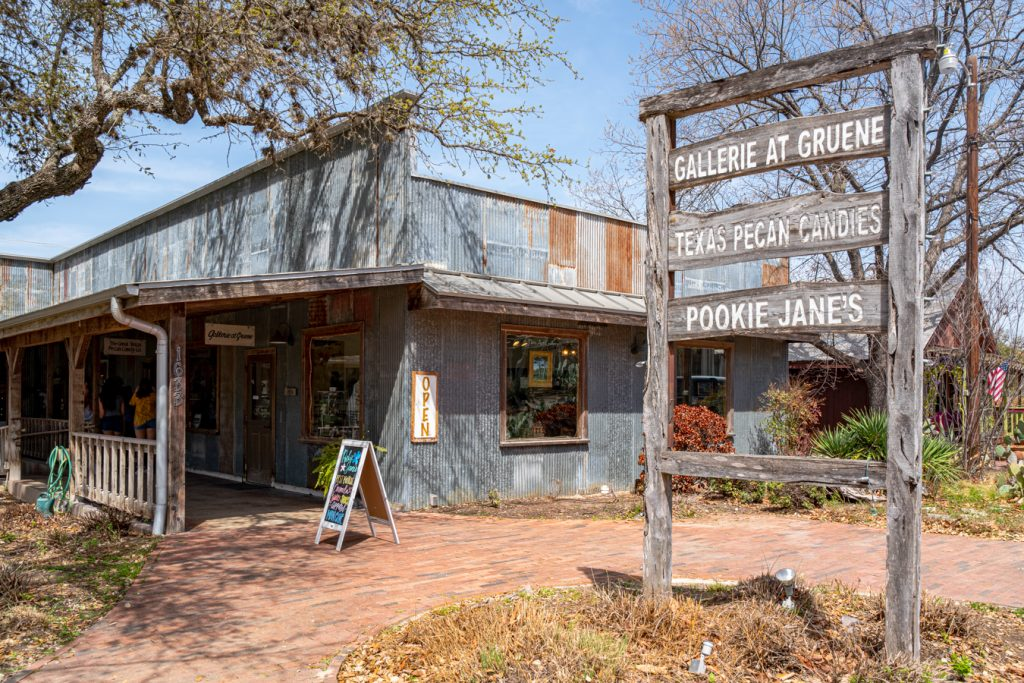 sign for the great texas pecan company and other shops in historic downtown gruene texas