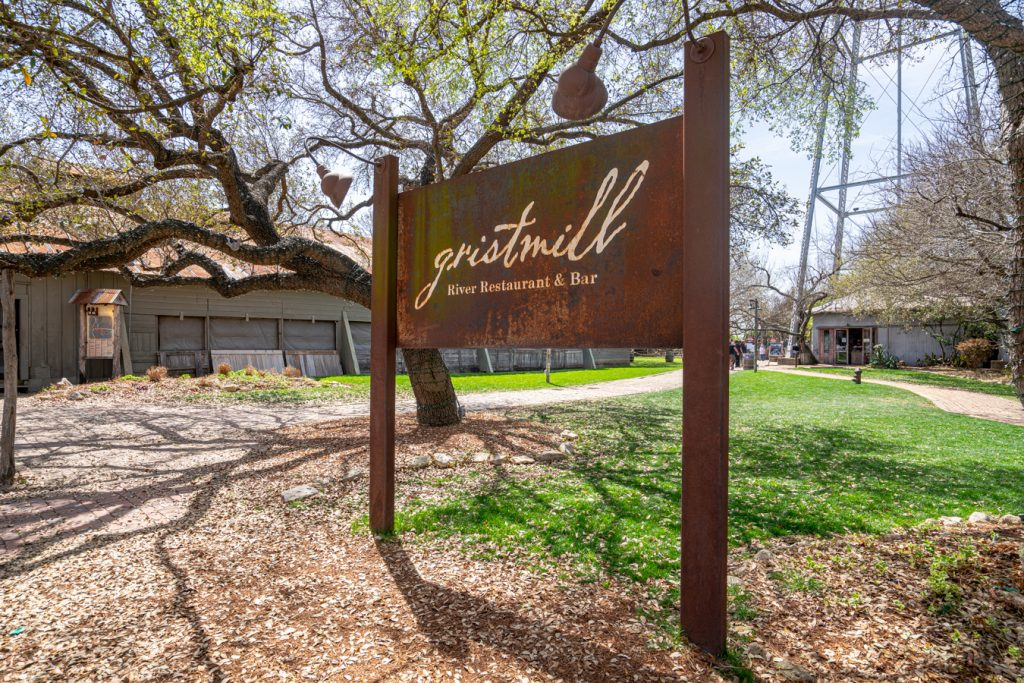 "iron photo of sign reading ""gristmill"" under an oak tree, one of the best restaurants in gruene"