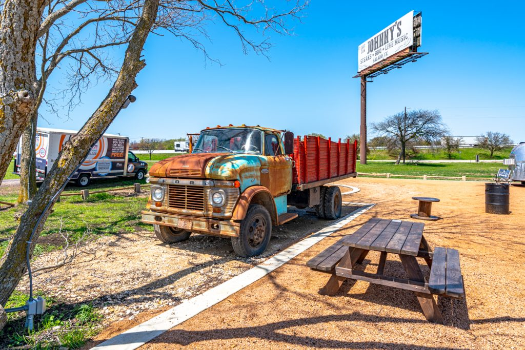 colorful historic truck parked at food truck park in jarrell tx next to a picnic table