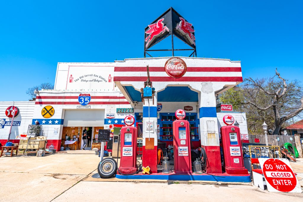 front facade of old jarrell gas station, painted red and white