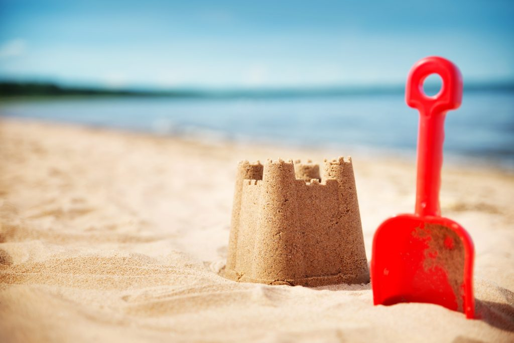 small sandcastle displayed with a red shovel on a sandy beach