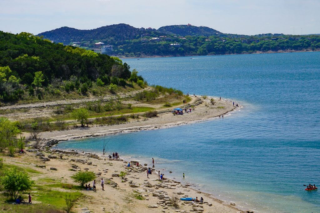 view of people enjoying one of the beaches near san antonio, as seen from overlook park on canyon lake
