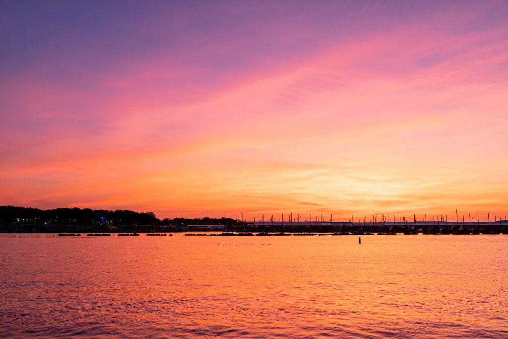 bright orange sunset over lake lewisville, home to one of the best beaches near dallas texas