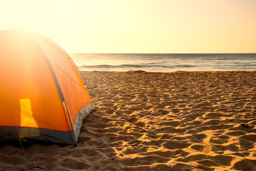 orange tent on the sand with water in the background at sunrise when beach camping texas