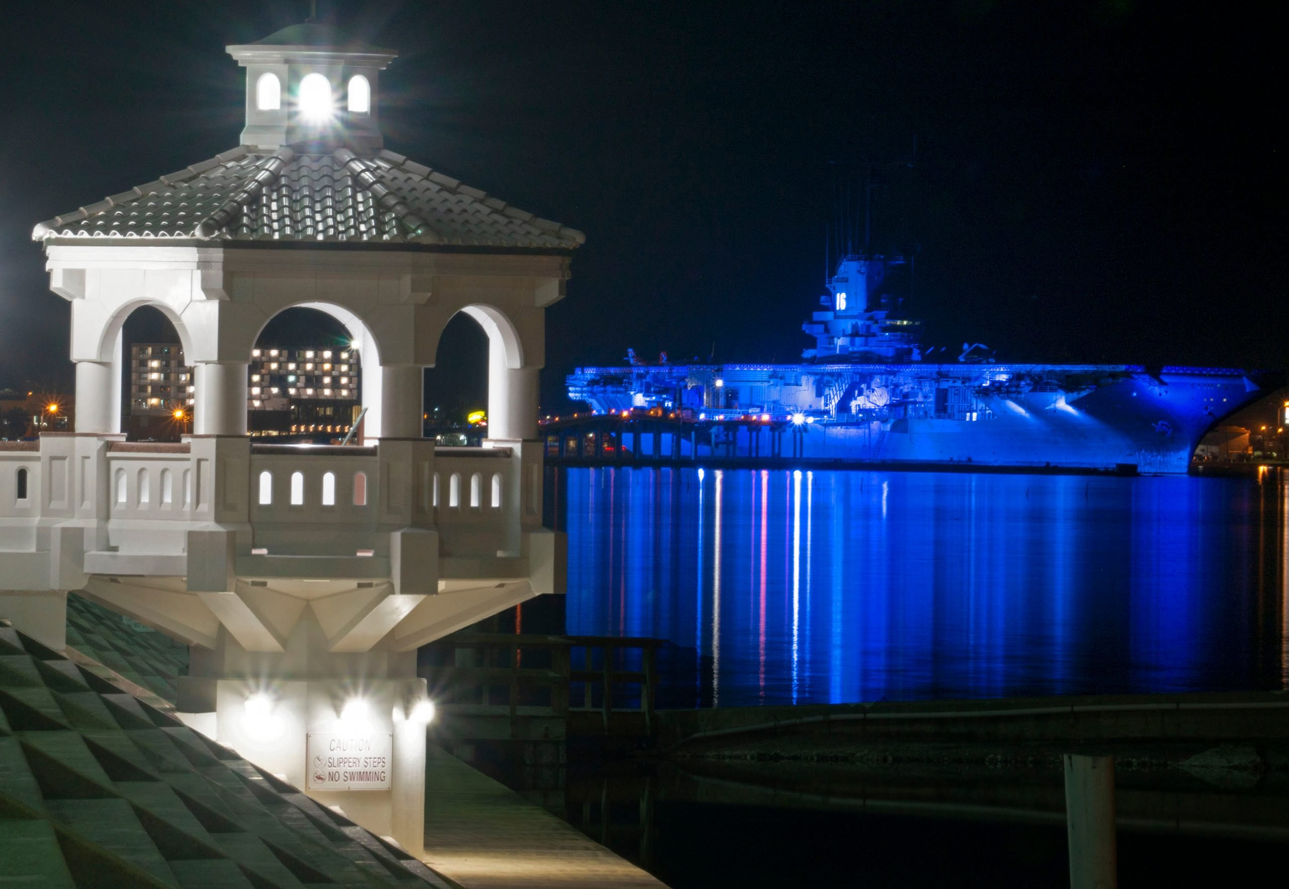 blue ghost of uss lexington lit up at night in corpus christi, one of the most haunted places in texas