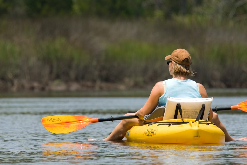 woman in a blue tank top paddling a yellow kayak in a marsh