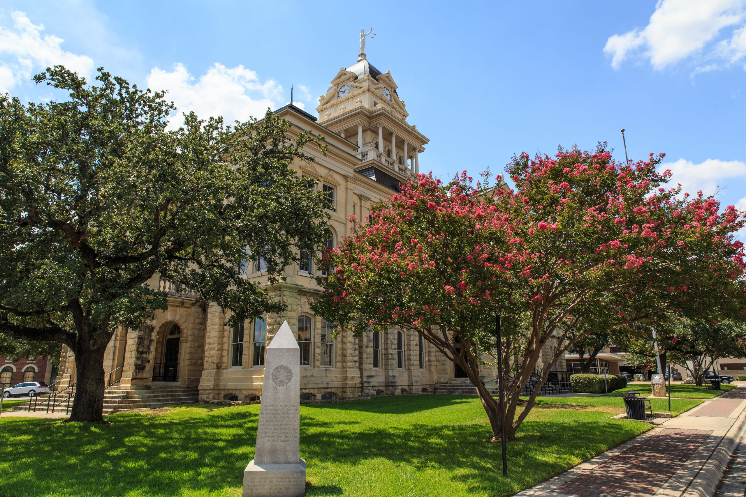 bell county courthouse with square, one of the best things to do in belton texas, with trees blooming pink flowers in the foreground