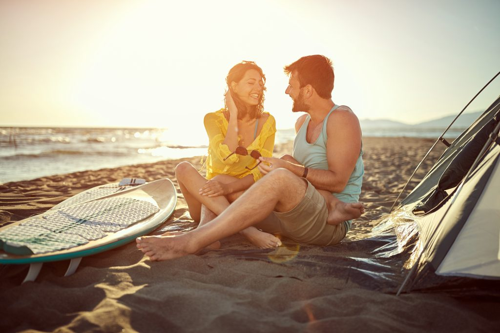 couple sitting on the sand next to a tent with sup boards, a fun possibility when you camp on the beach in texas