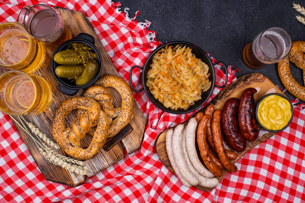 german style sausages and pretzels on a checkerd tablecloth shot from above