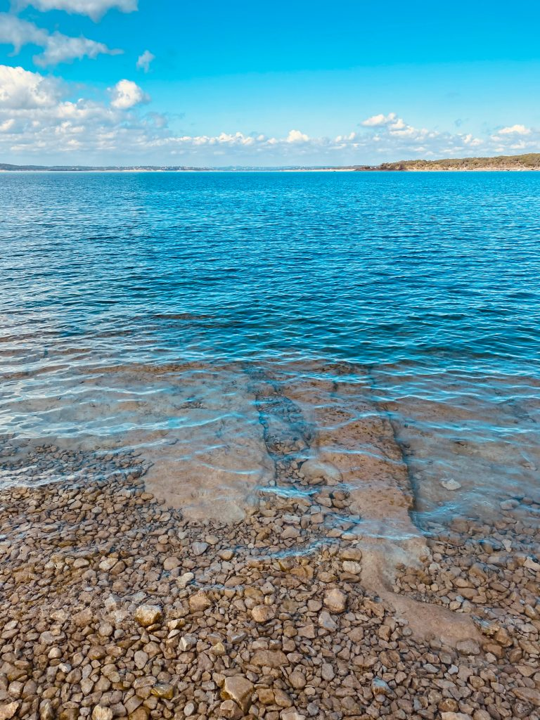 view of canyon lake from the shore, showing off clear pebble bottom of bright blue lake