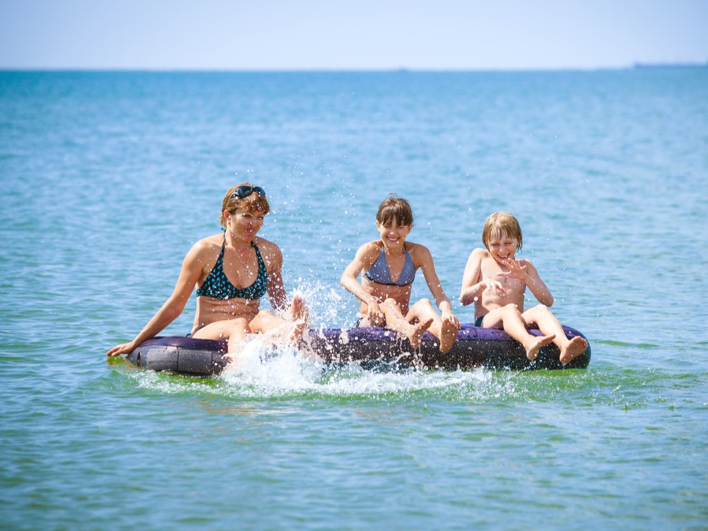 2 women and a small boy sitting on a black floatie in a lake having fun at a beach day