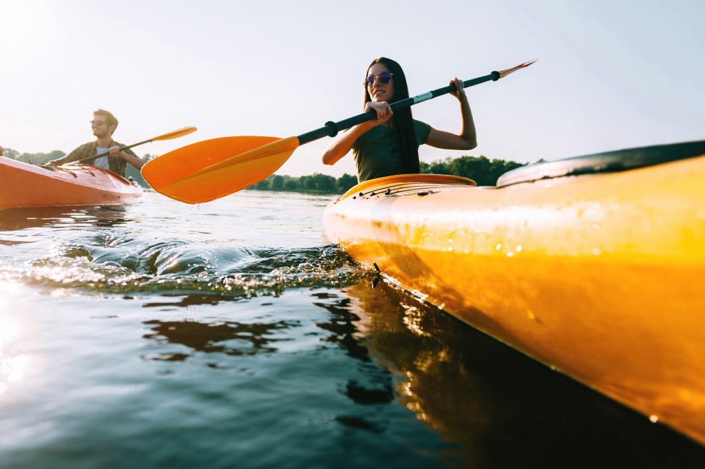 couple kayaking on a lake, with a yellow kayak taking up most of the shot