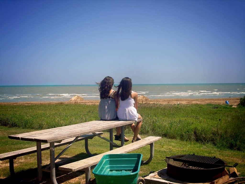 two women sitting a picnic table overlooking a beach in tx