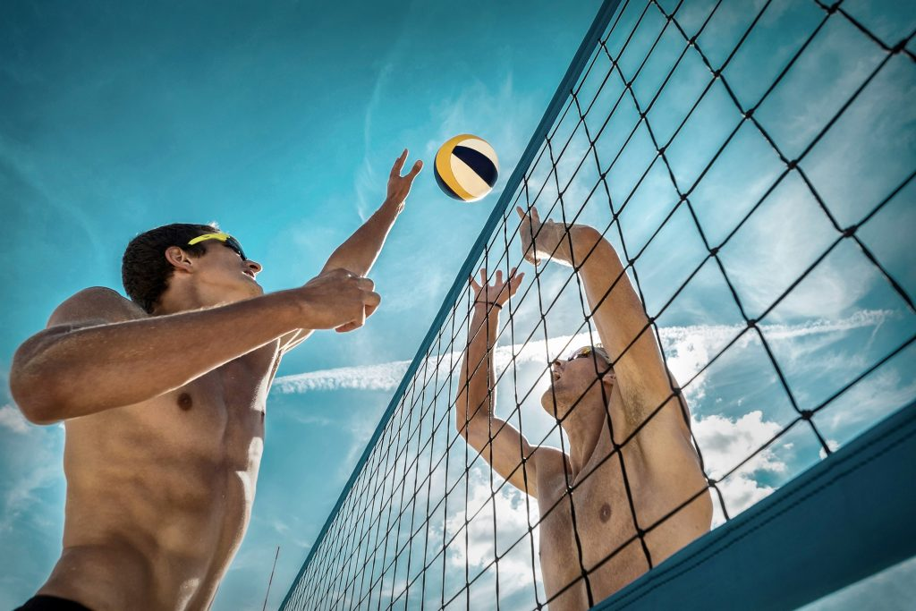 two men jumping up to the net while playing beach volleyball