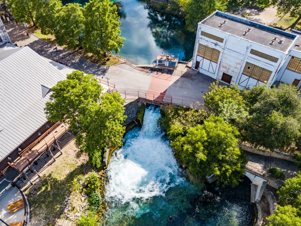 aerial view of the comal river passing under a bridge in new braunfels, one of the texas german towns