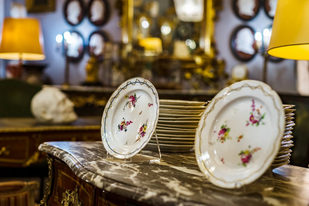 plates painted with flowers for sale in an antique shop