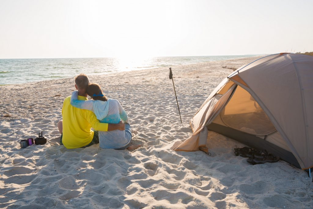 couple sitting facing the ocean next to a tent on a sandy beach when texas beach camping