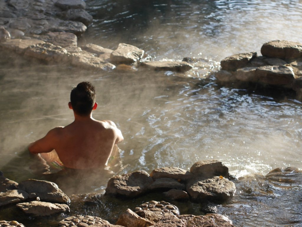 man sitting in a hot spring that is a stone pool