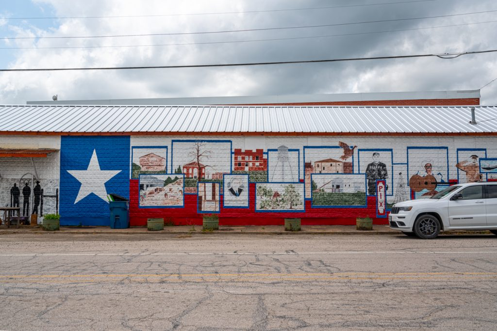 historic mural painted with background of a texas flag on the side of the building