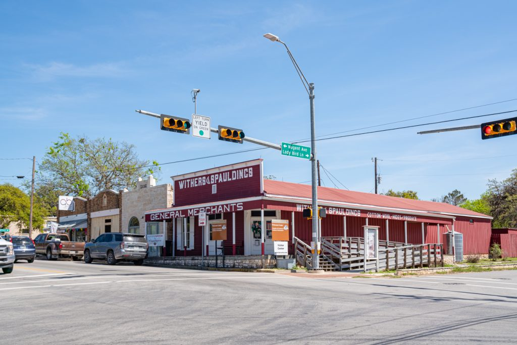 street corner in johnson city texas with traffic light in the foreground and red general store in the background
