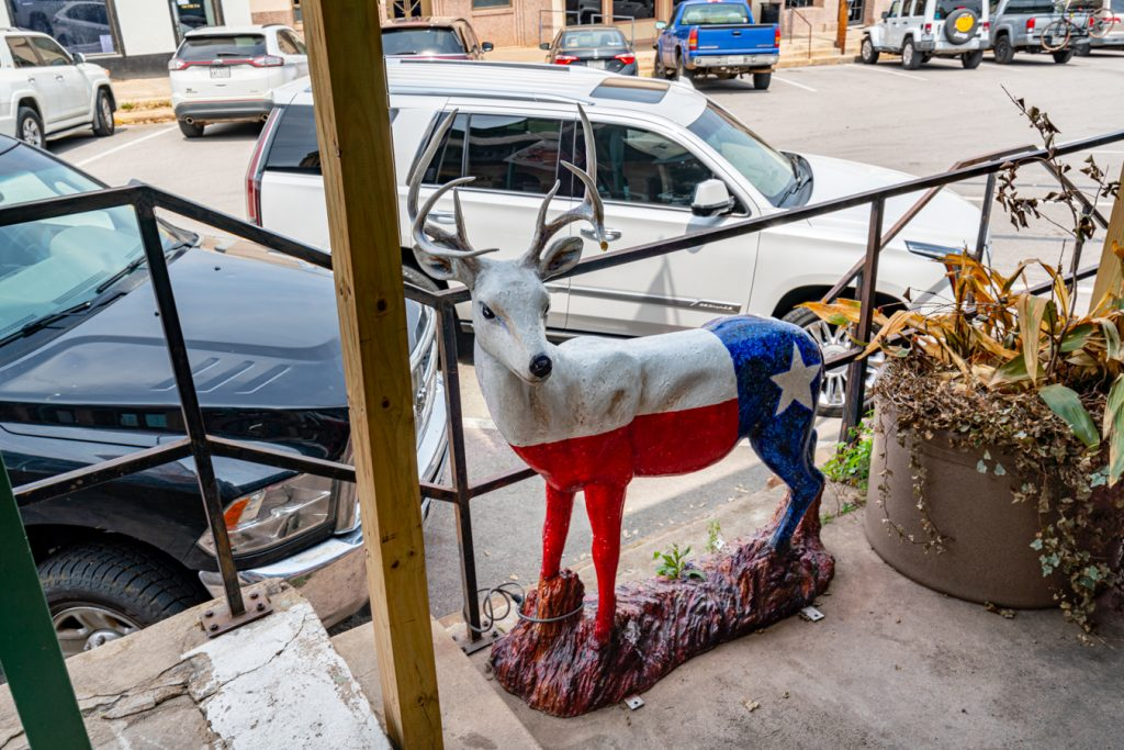 llano deer statue painted in the form of a texas flag