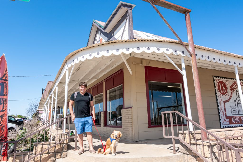jeremy storm and ranger storm standing in front of an antique store, one of the best places to visit in muenster tx