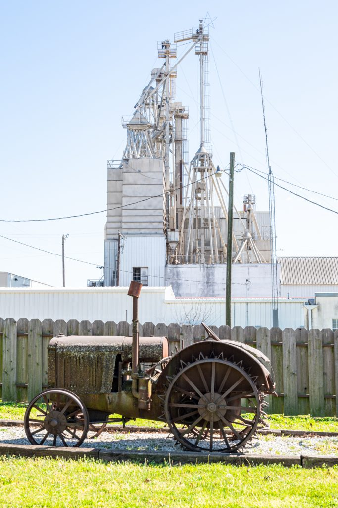 antique tractor in muenster texas with the working mill visible behind it