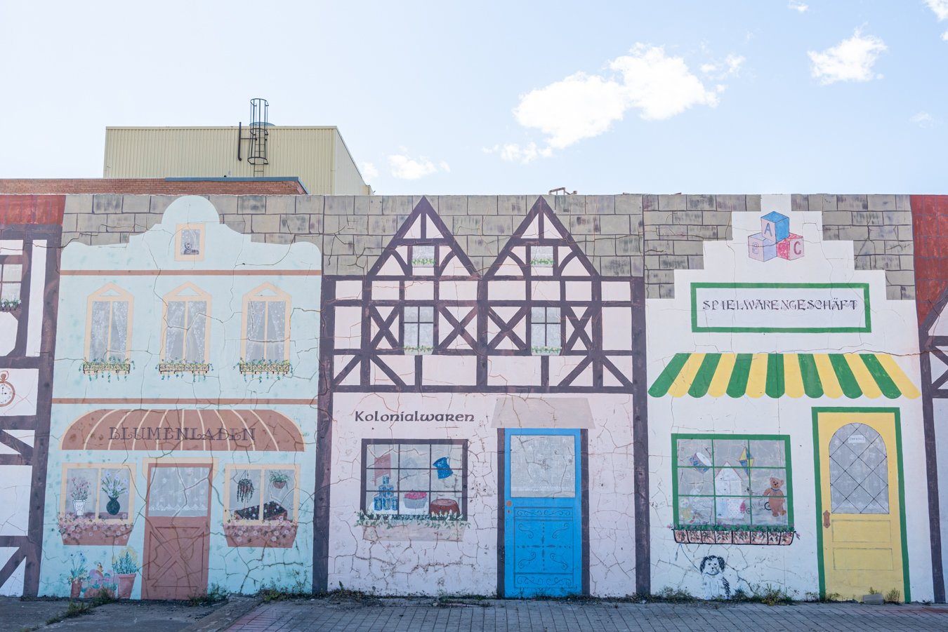 mural displaying painted german-style buildings, one of the best things to do in muenster texas is snap photos here