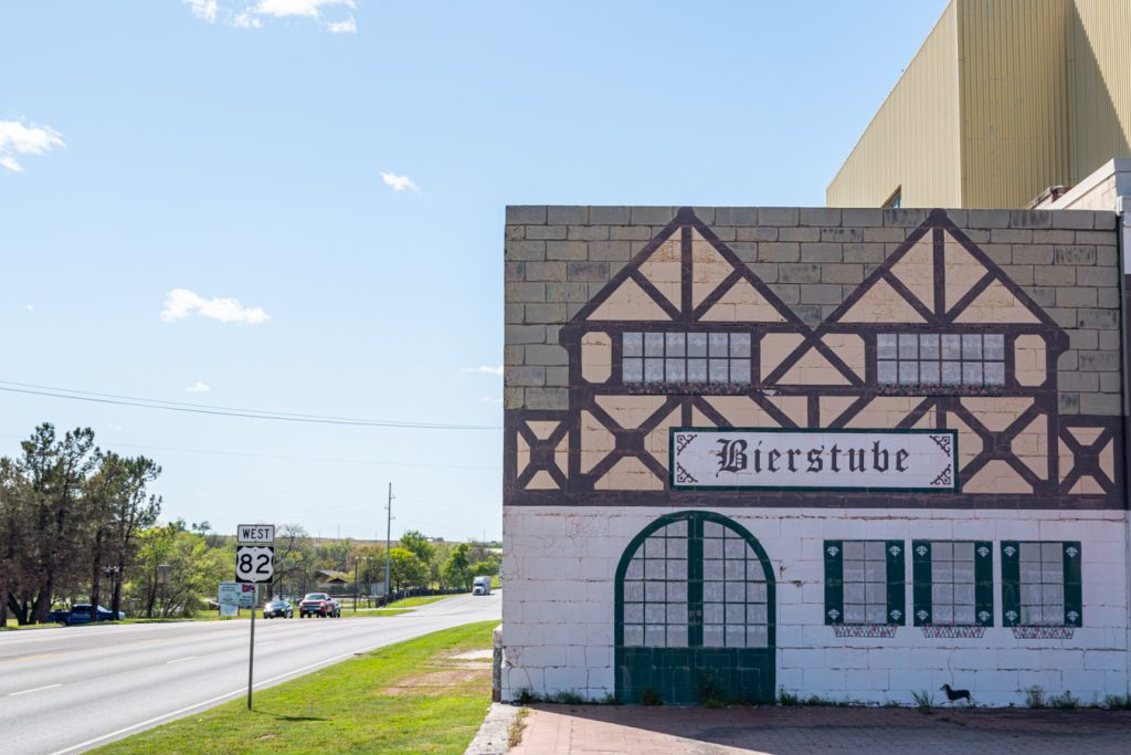 german mural of a building on the side of highway 82 in muenster tx