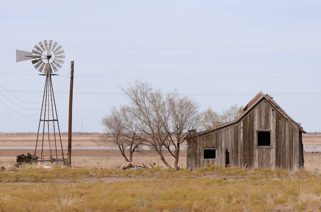 abandoned wood home and windmill in texas