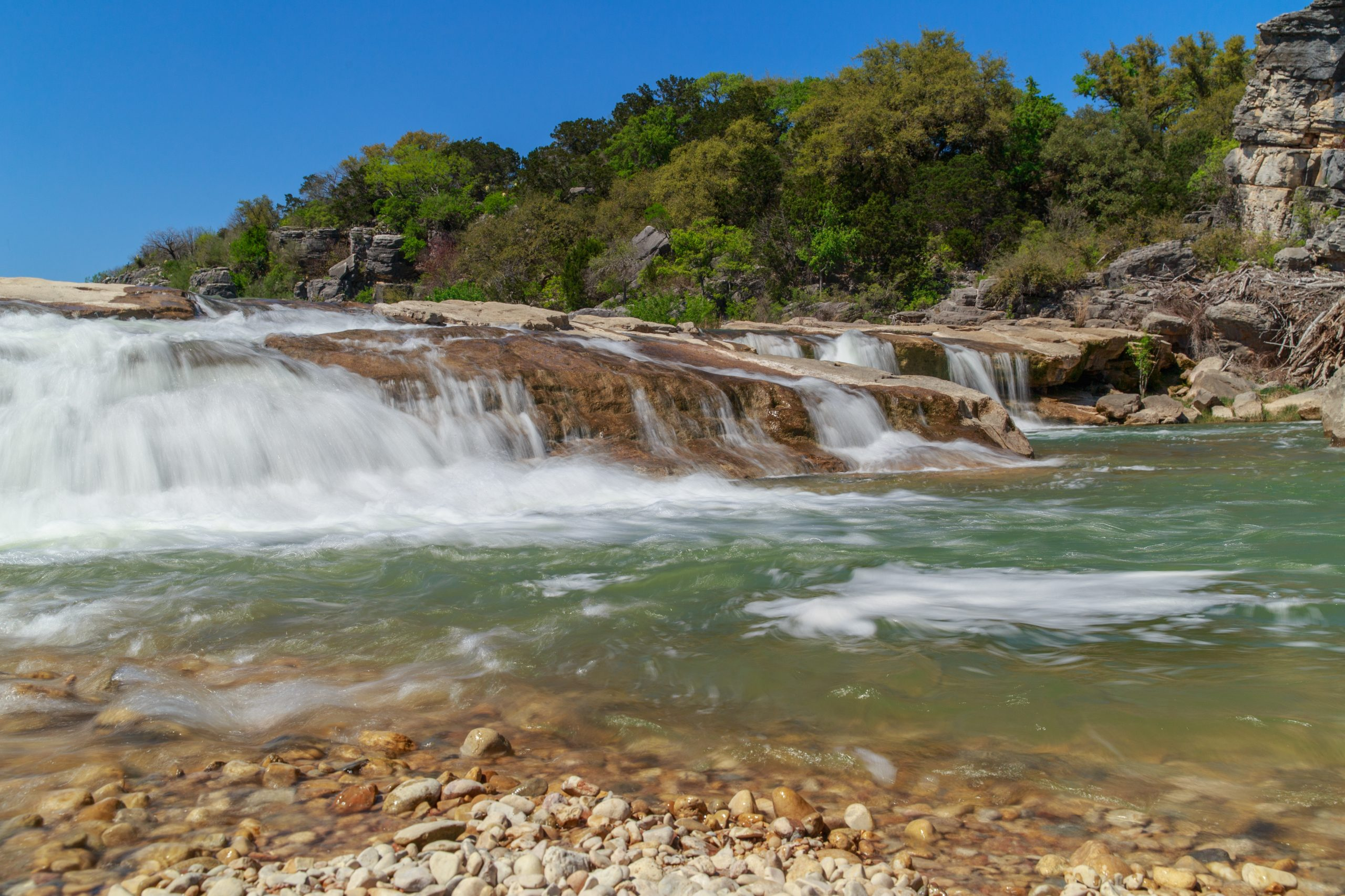 small waterfall in pedernales falls state park, one of the best state parks in texas