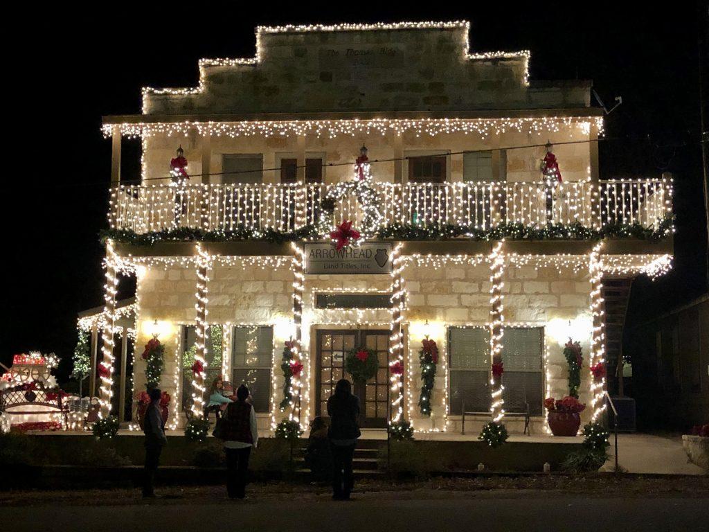 limestone building in johnson city lights festival, lit up at night in december
