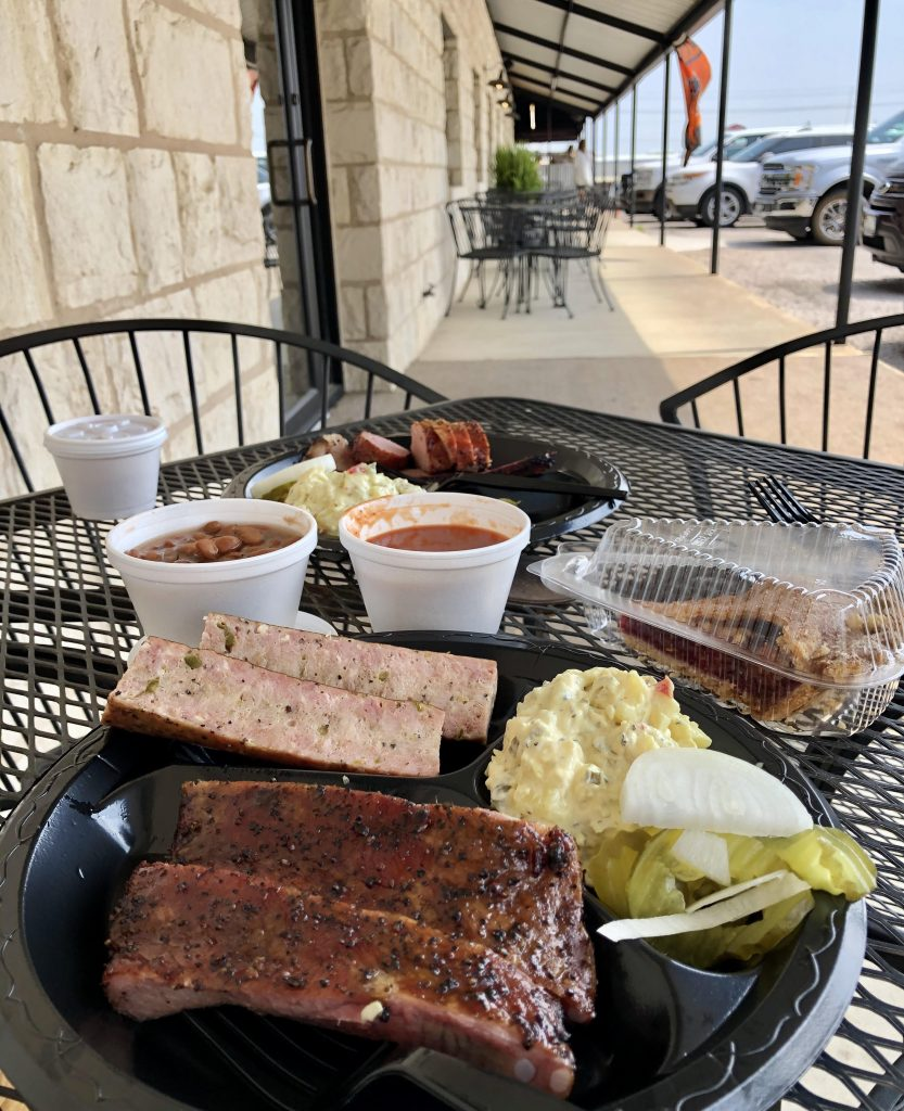 plate of barbecue from inmans kitchen being eaten at a black metal table on the front porch of the llano restaurant