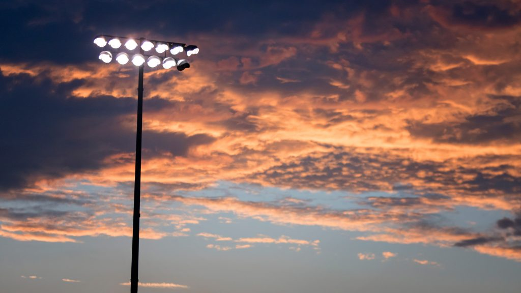 stadium lights over a sunset in texas, similar to one of the best texas tv shows friday night lights