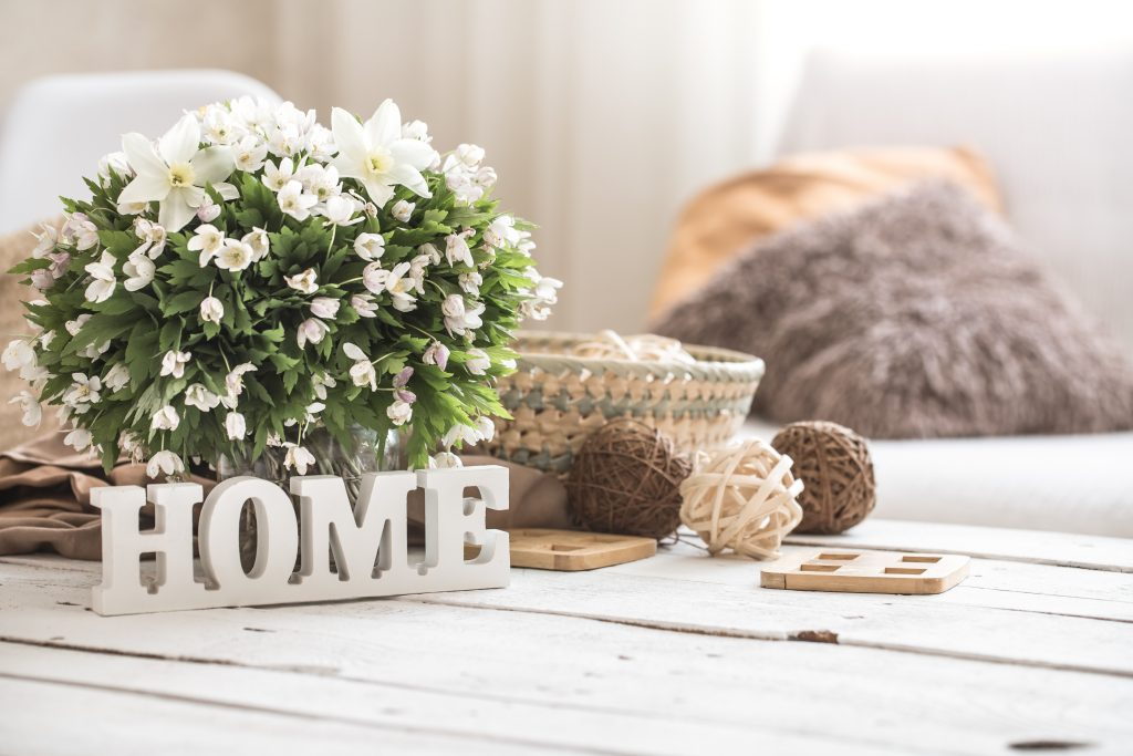 """famrhouse style coffee table decorated with flowers and a white sign reading """"home"""""""