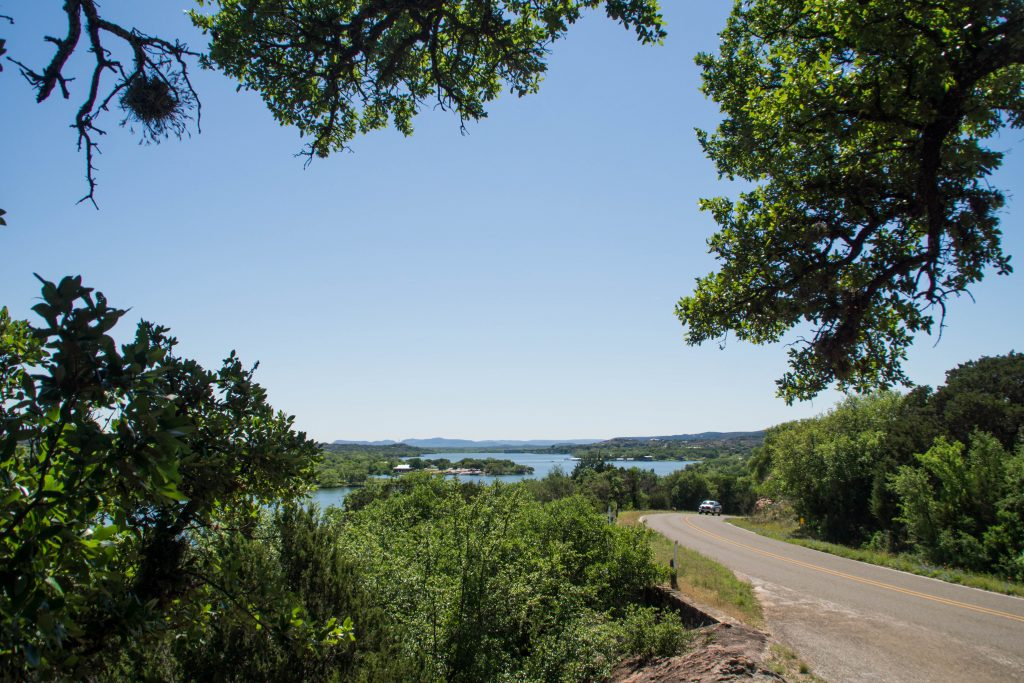 inks lake as seen from above with a road in the foreground, one of the best day trips in texas
