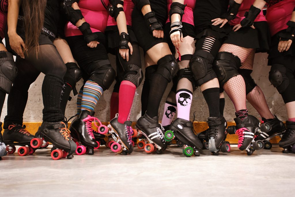 the legs of a group of women suited up for roller derby, as seen in the rollergirls tv show filmed in texas