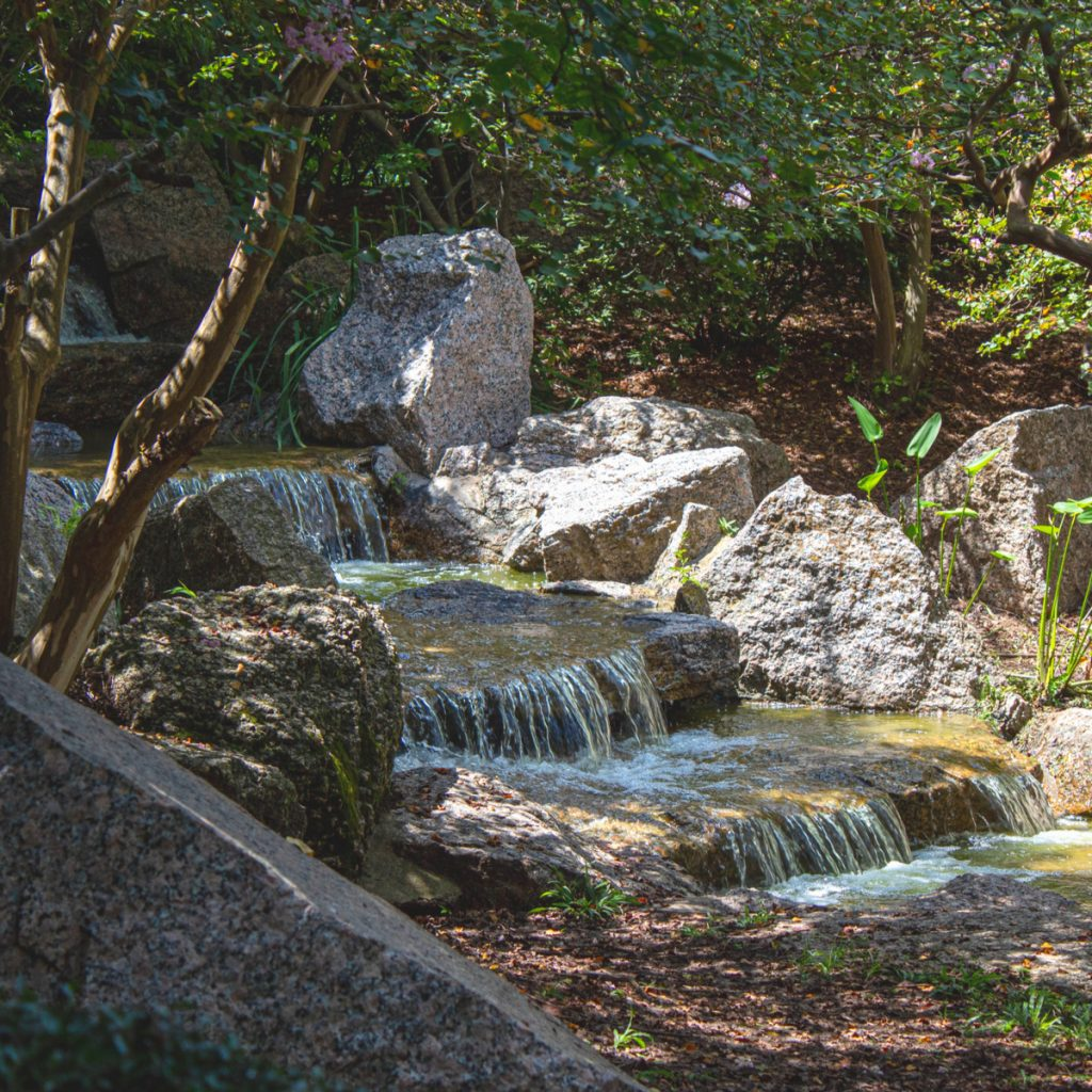 cascading waterfall under the trees at japanese garden houston texas