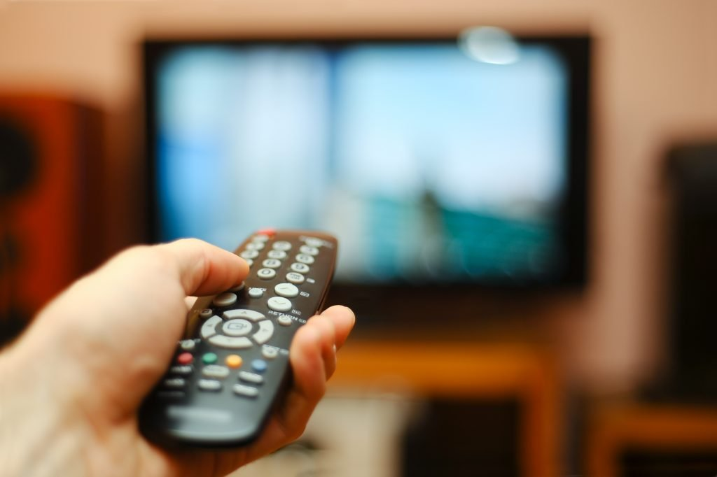 hand holding a remote pointing at a tv in the background