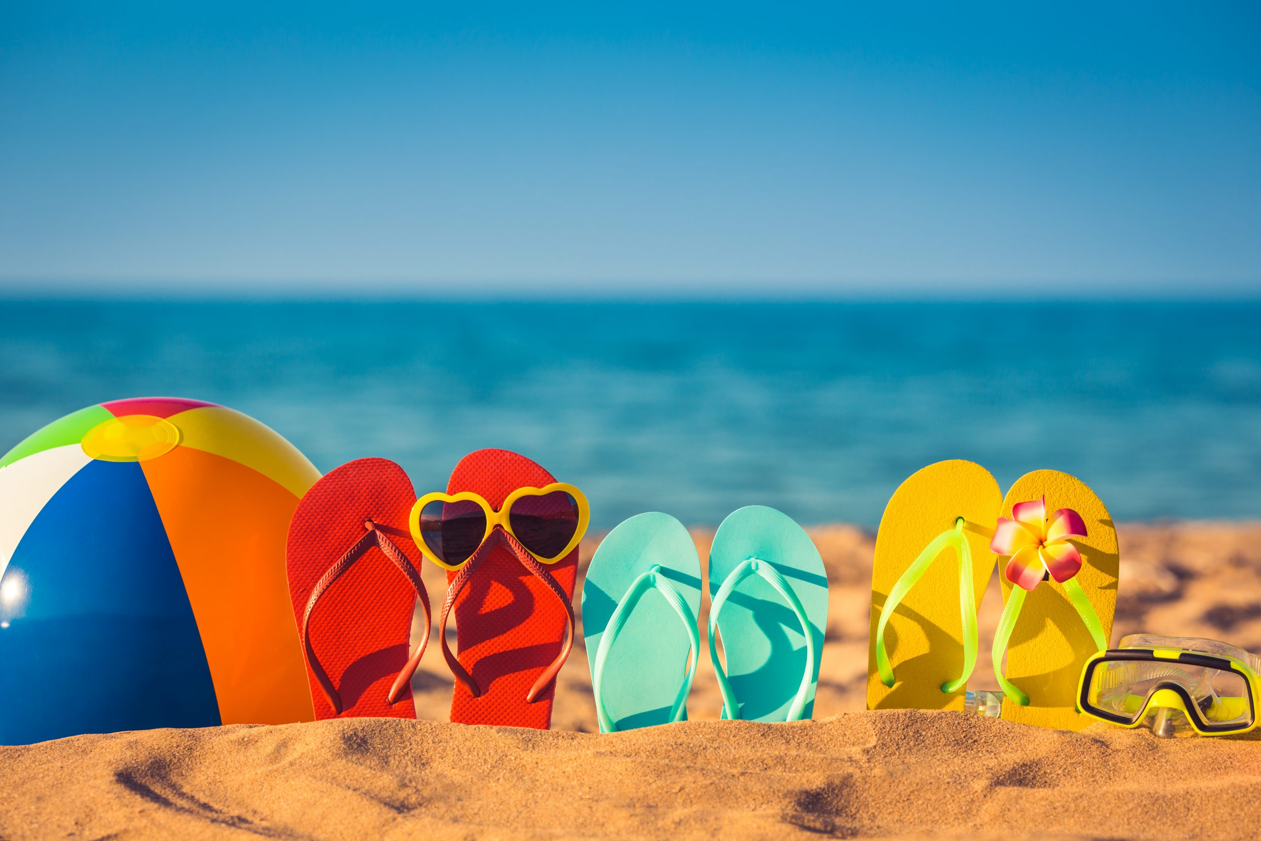 collection of coloful flipflops on a beach, reminiscent of summer in texas activities