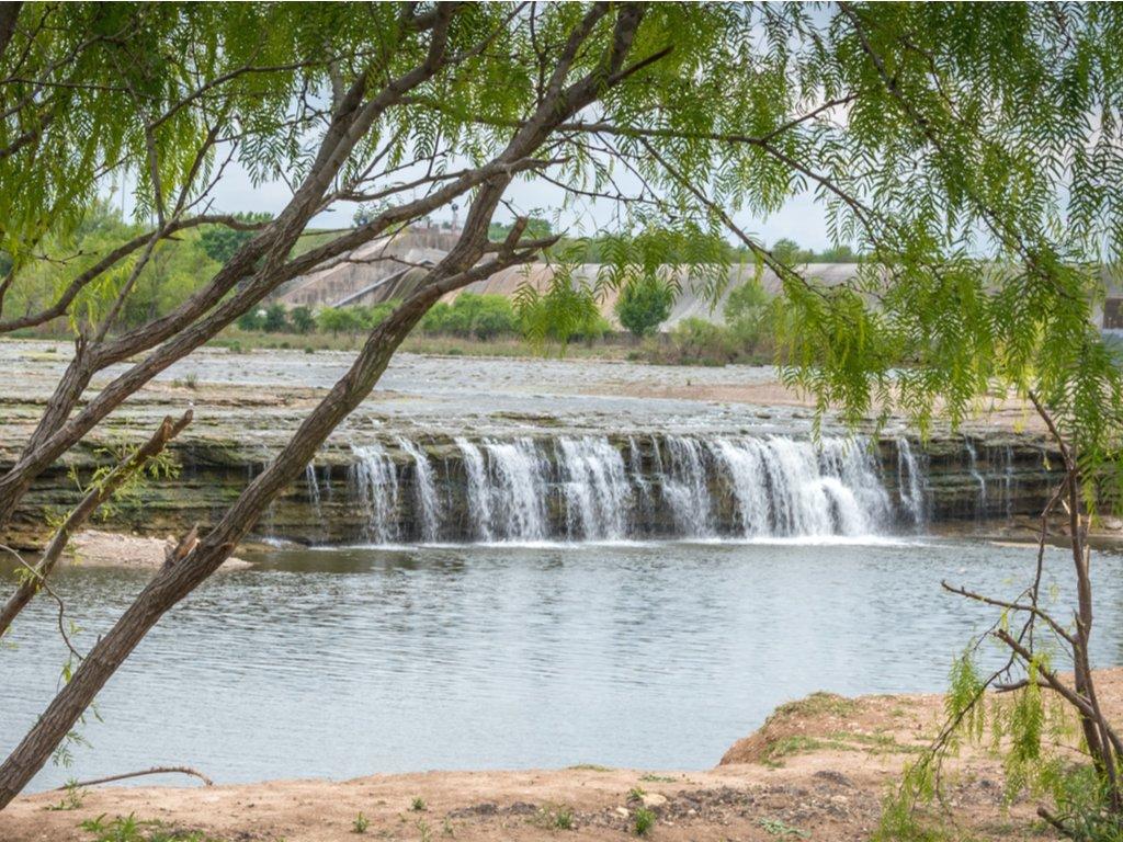 dallas fort worth waterfalls as seen through green leafy tree