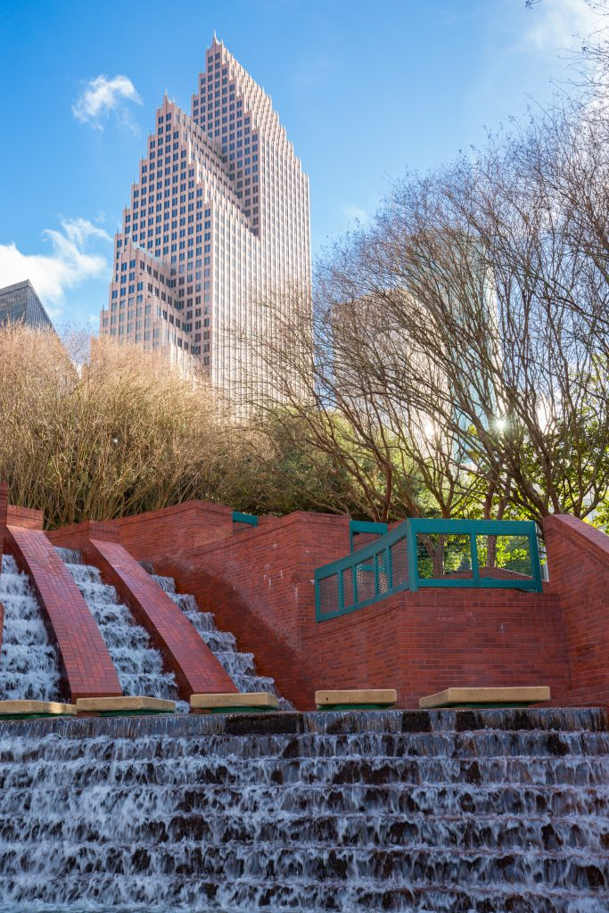 waterfalls in houston tx at Sesquicentennial Park with skyscraper in the background