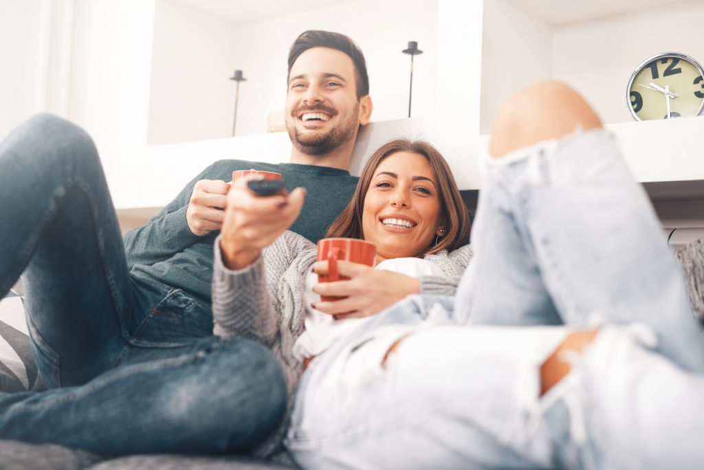 couple wearing jeans, sitting on a couch and laughing at the tv series together